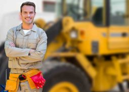 Un travailleur dans le bâtiment debout avec les bras croisés devant un bulldozer.