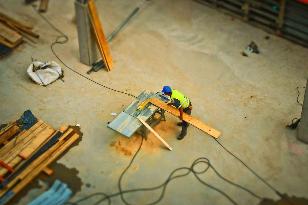 Un travailleur du bâtiment qui est entrain de couper du bois.