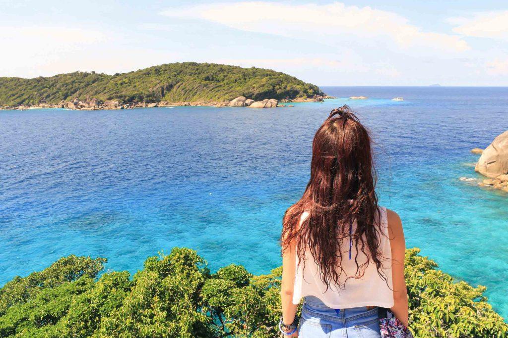 Une jeune femme qui contemple l'horizon, au bord de l'eau.