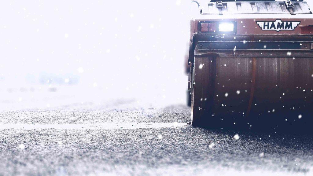 Un rouleau compresseur en fonction sous des flocons de neige.