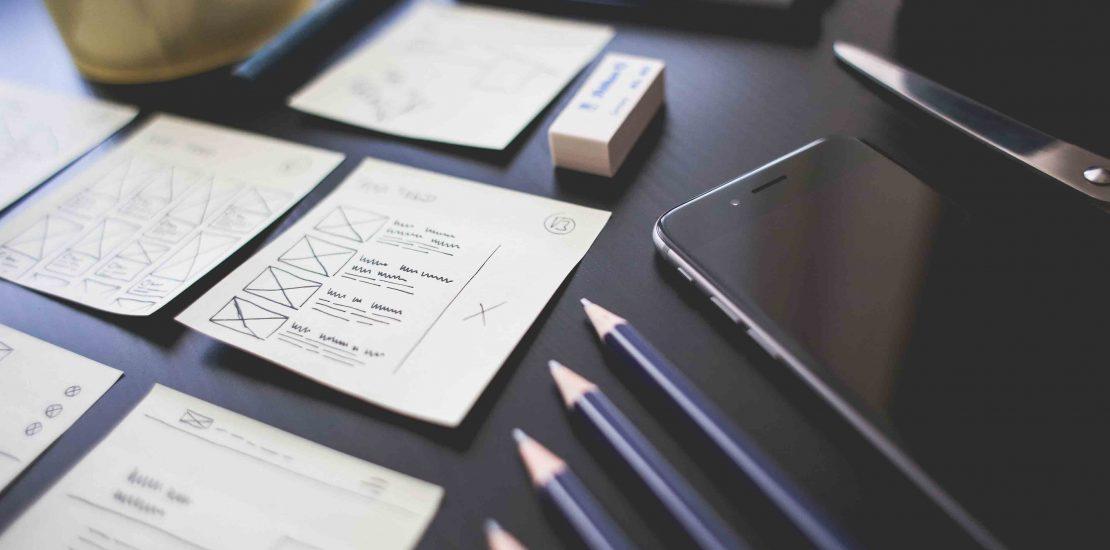 Un bureau avec un iPhone, stylos et feuilles.