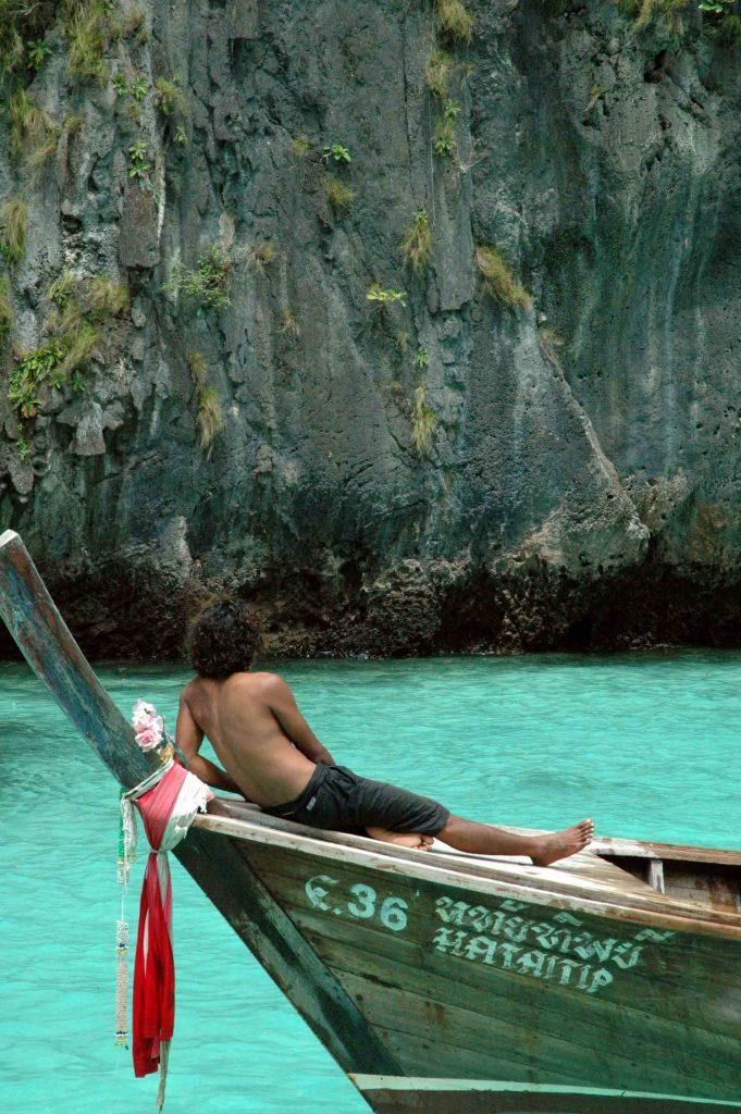 Un touriste torse nu allongé sur son bateau.